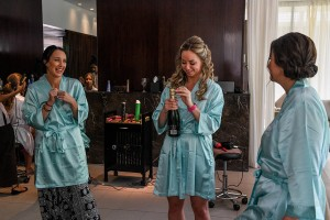 A bridesmaid pops open the champagne bottle