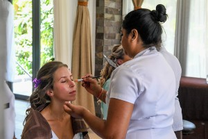 A bridesmaid closes her eyes as her makeup is touched up