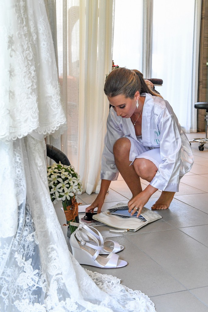 The bride packs her items in her clutch before the wedding