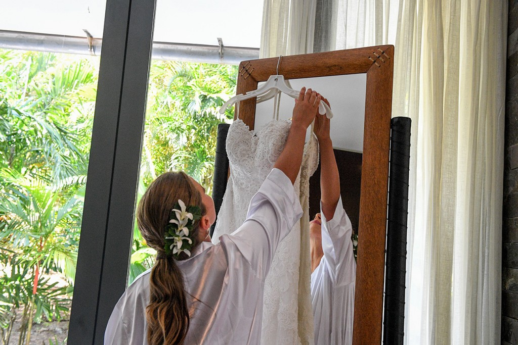 The bride lifts her wedding dress off a hook on the mirror