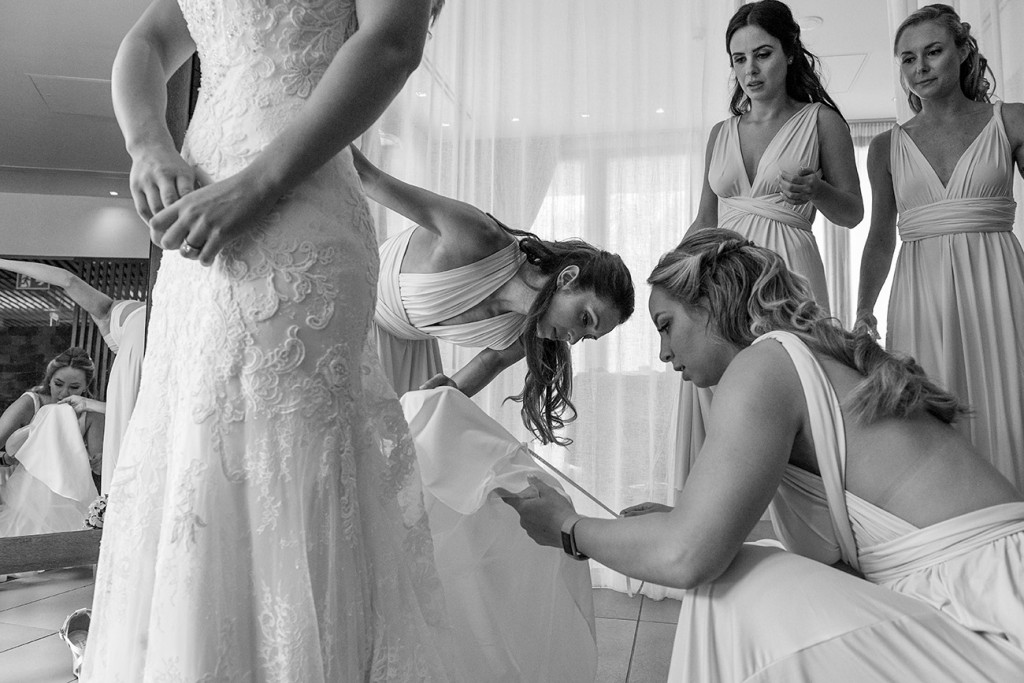 Bridesmaids help the bride into her dress