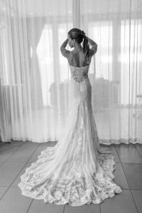 A monochrome full length image of the dressed bride