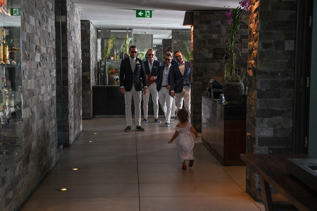 The daughter of the couple runs towards the groomsmen