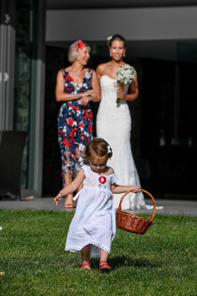 The cute flower girl walks down the aisle ahead of the bride