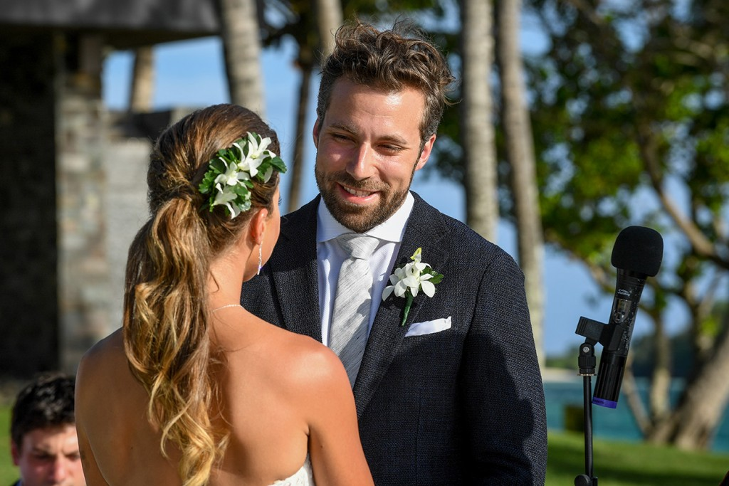 The groom looks lovingly at his bride as he says his vows