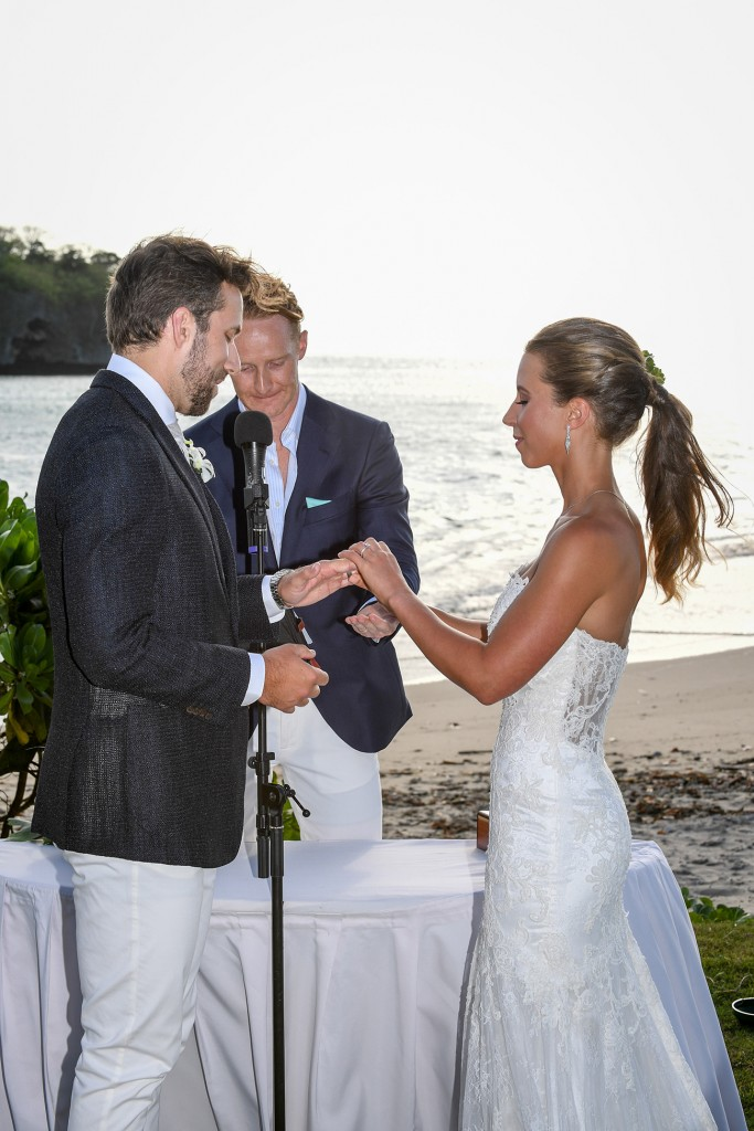 The bride slips a ring onto her groom's finger