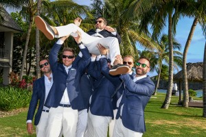 The groomsmen lift the groom above their head