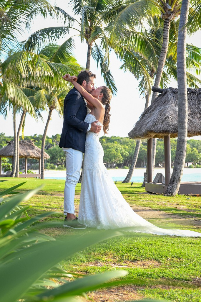 The newly-weds kiss under the palm trees at the Intercontinental Fiji