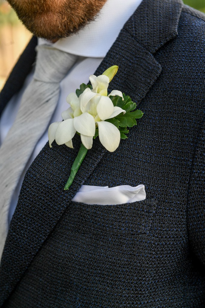 A closeup of the groom's fresh flower frangipani boutonniere