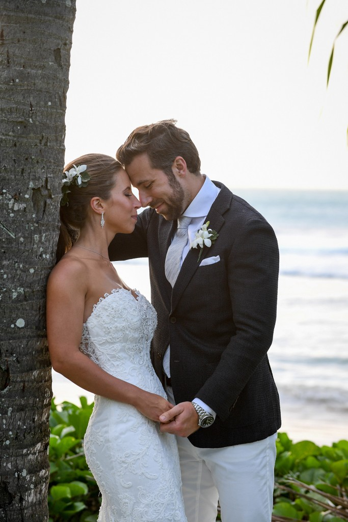 The newly weds share an intimate moment against a palm tree