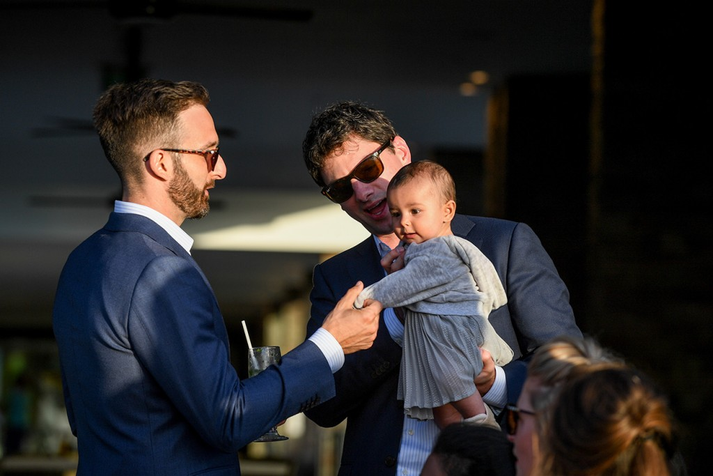 Wedding guests play with a cute baby girl at the wedding party