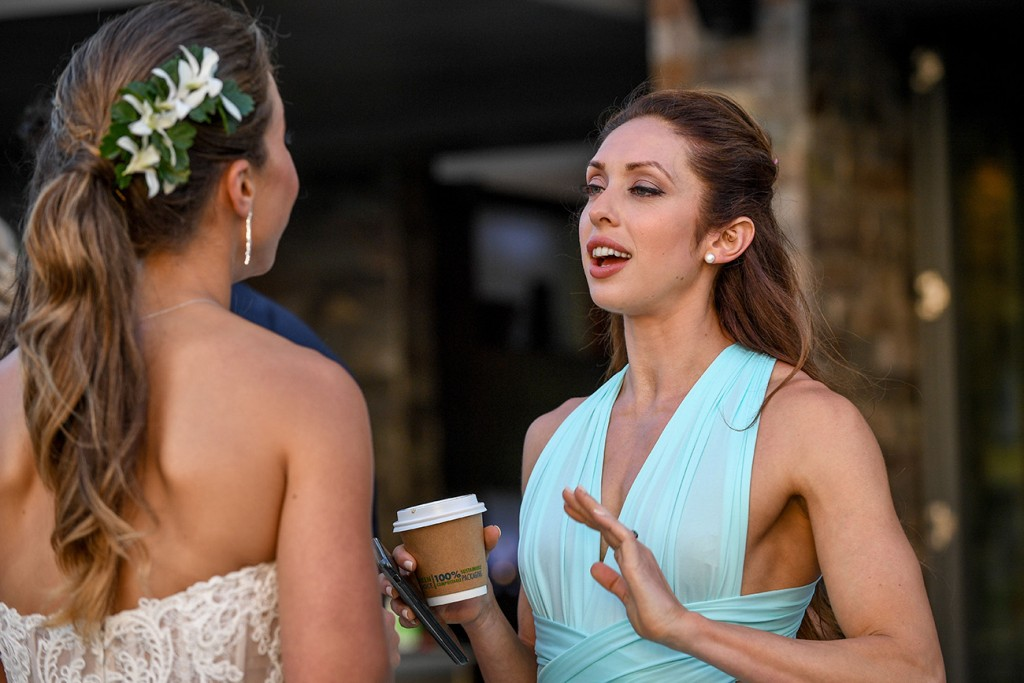 A bridesmaid animatedly chats up the bride