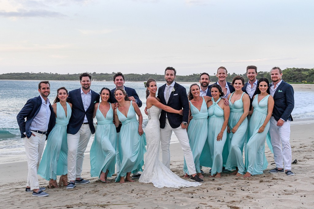 The bridal party poses for a photo on the beach