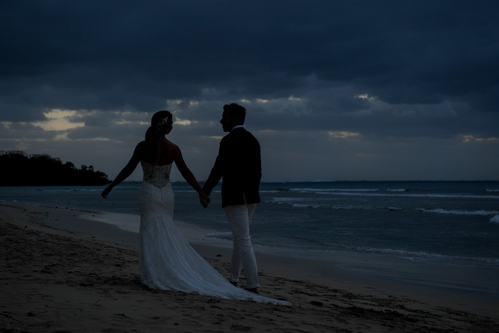 The newly weds stroll on the beach after dark