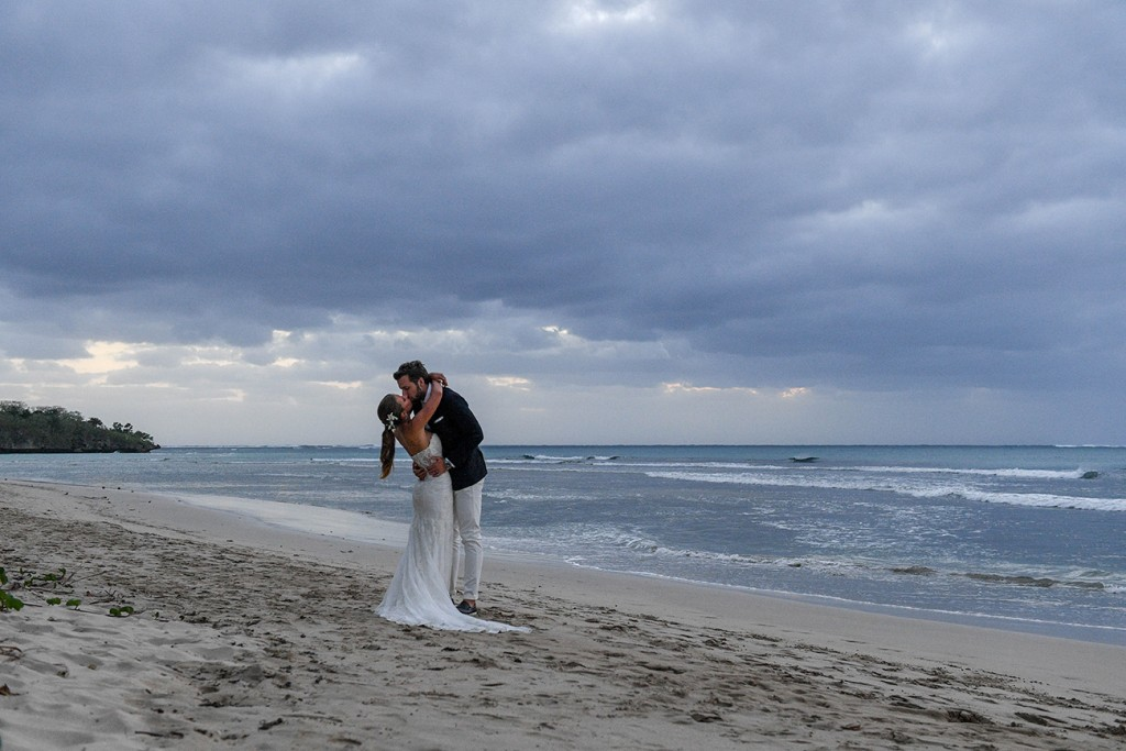 The newly weds kiss on the shore against a Fiji sunset