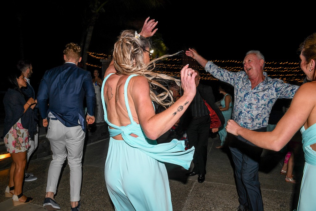 Wedding guests dance under fairy lights at the reception