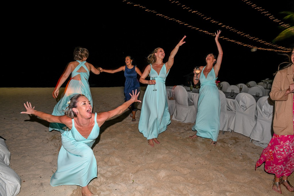 The bridesmaids dance crazily at the beach wedding reception
