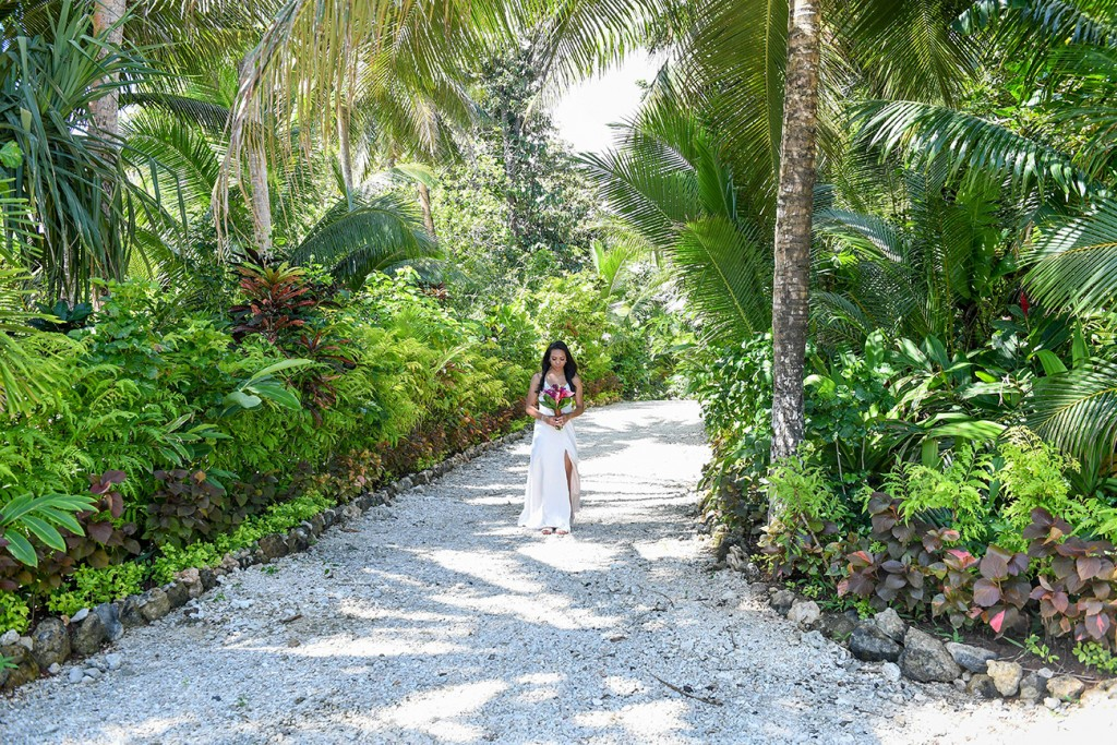 The bride walks down an aisle of palm trees