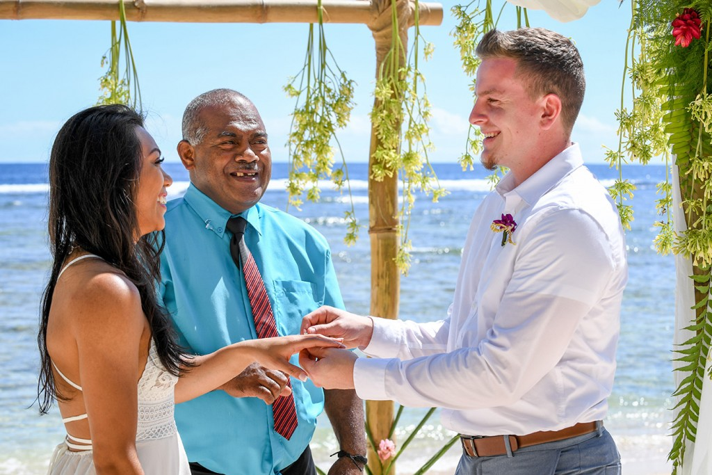 The overjoyed groom slips a ring onto his jovial bride's finger