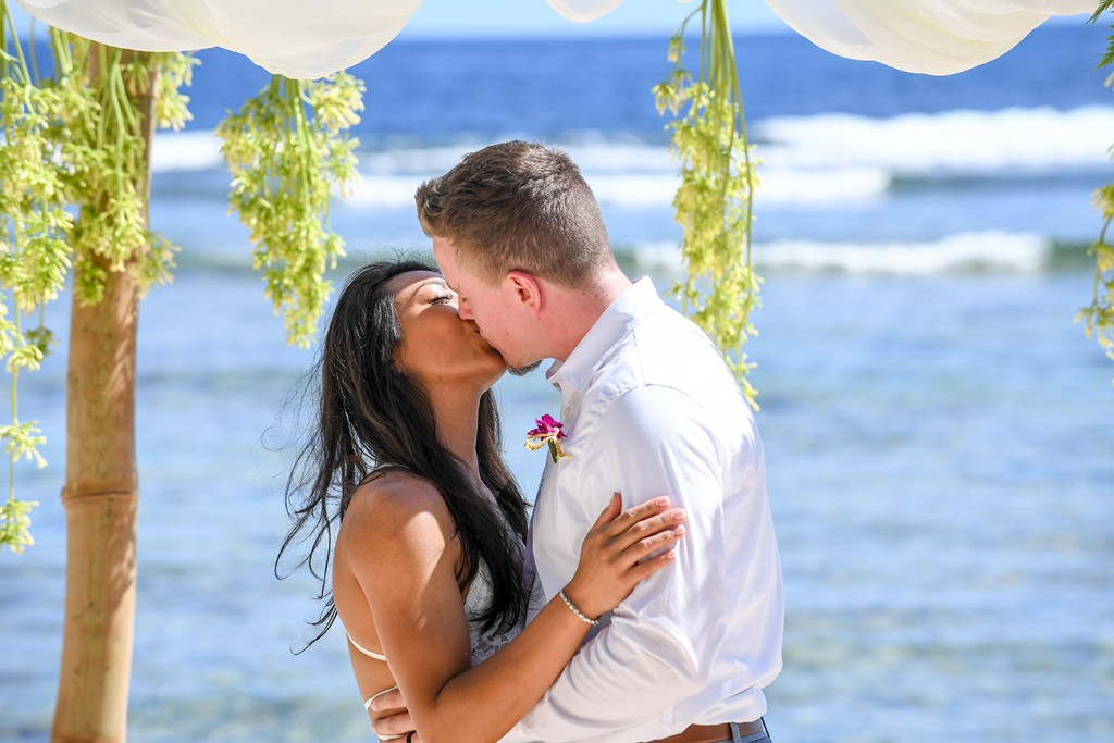 The married couple kiss under the bamboo altar at the Pacific Ocean