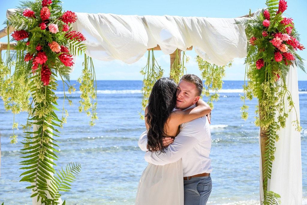 The newly weds hug against the azure ocean