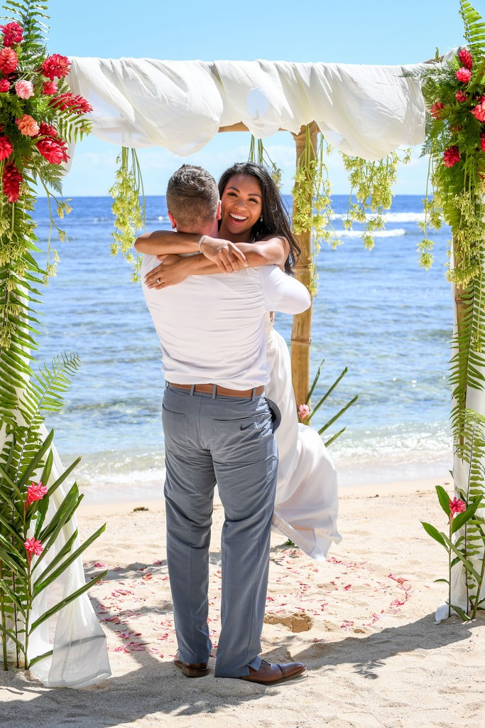 The groom lifts his bride in celebration at the shores of Savasi resort