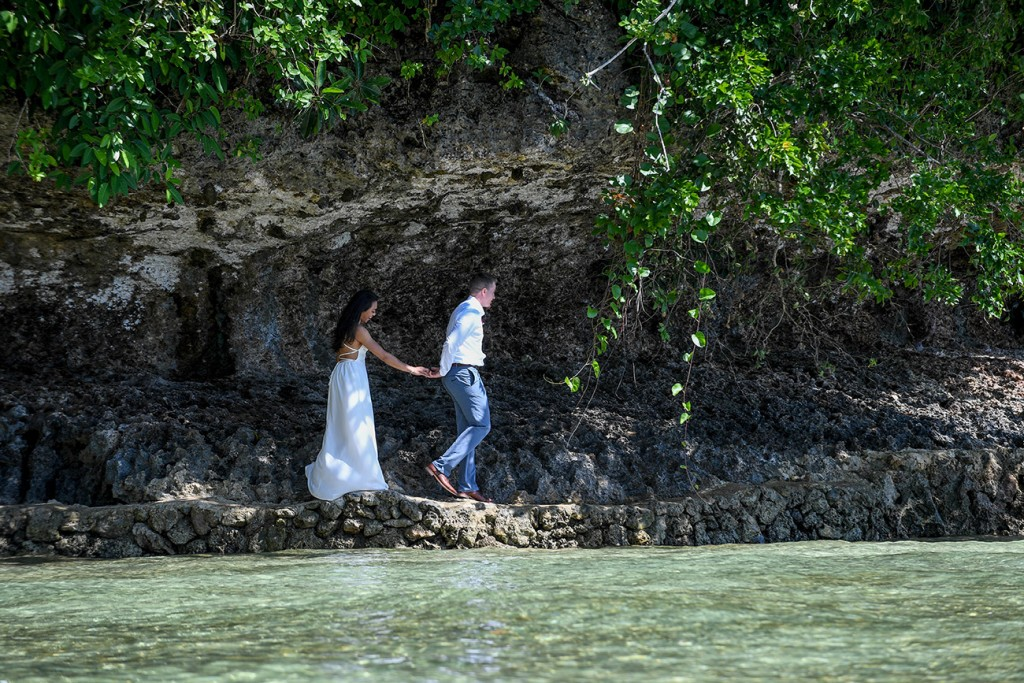 The newly married couple walks over rocks by the azure Pacific Ocean