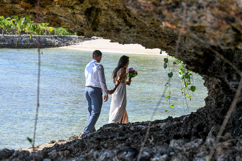 The bride leads her groom behind the coral rocks at Savasi Fiji