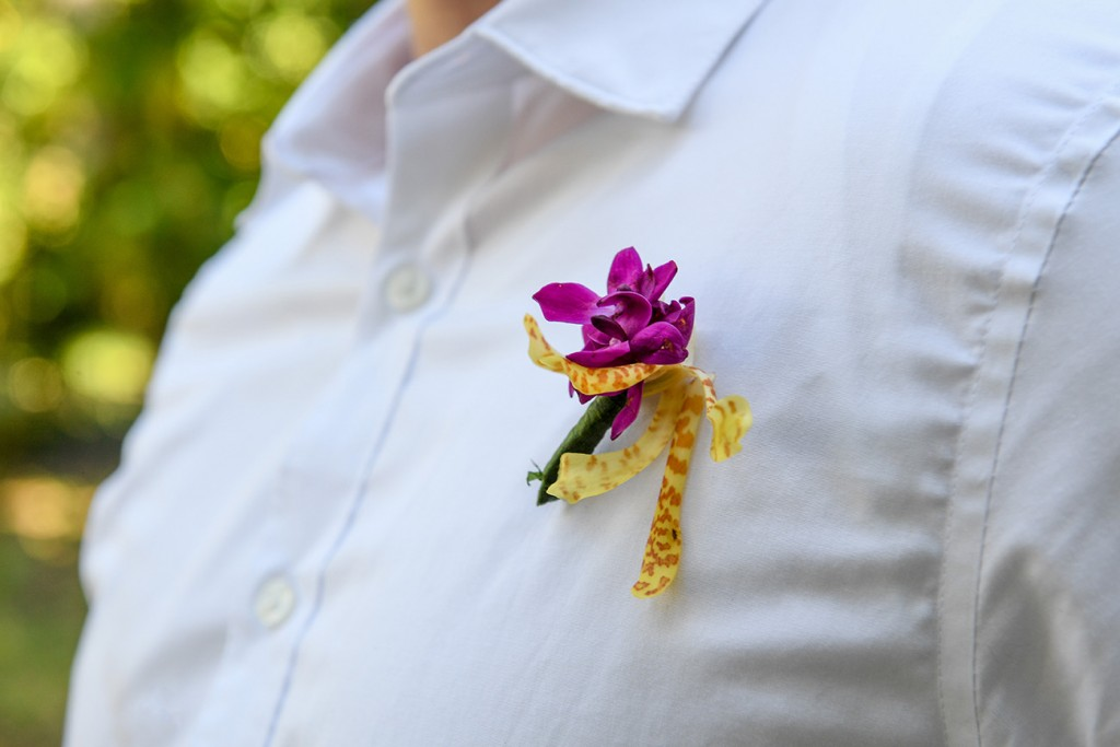 A closeup of the pink fresh flower boutonniere on the grooms shirt