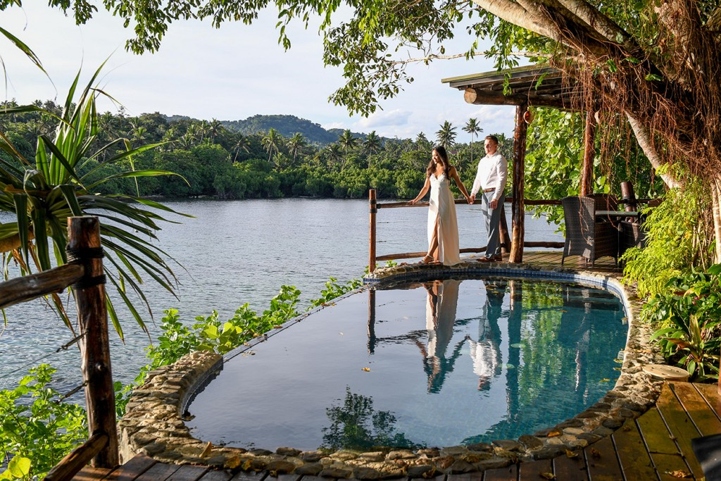 The groom and bride stare into the sunset standing next to a tiny infinity pool
