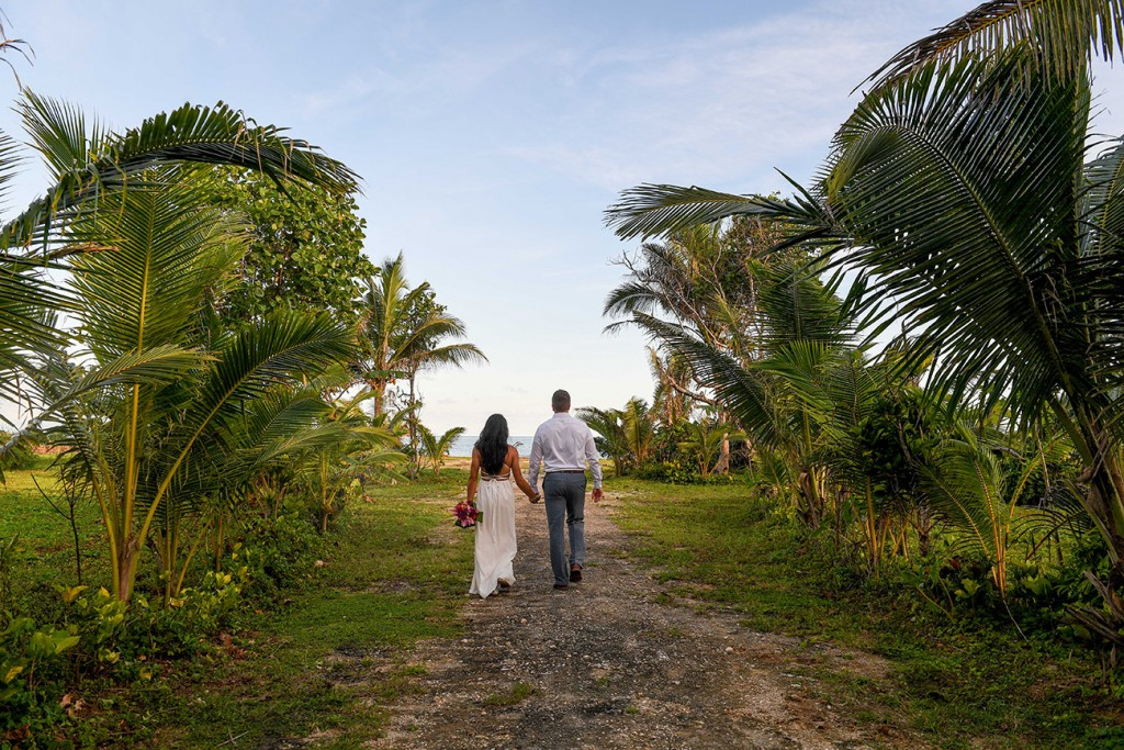 The couple strolls through palm trees