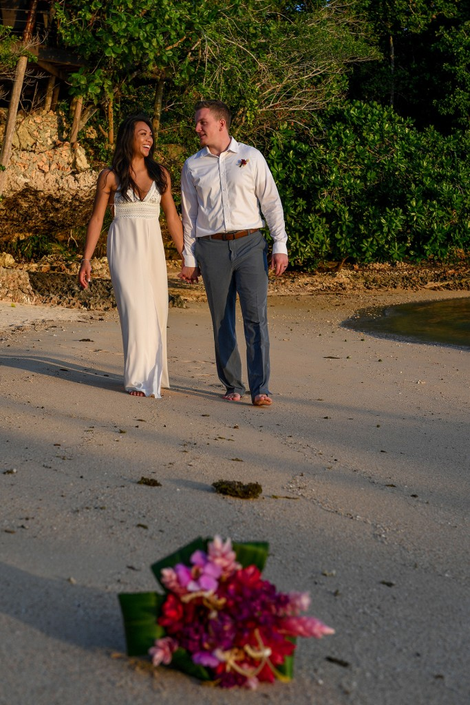 The groom makes his bride laugh as they stroll on the beach