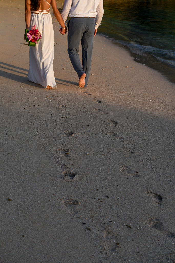 The newly-weds leave footprints as they stroll on the beach