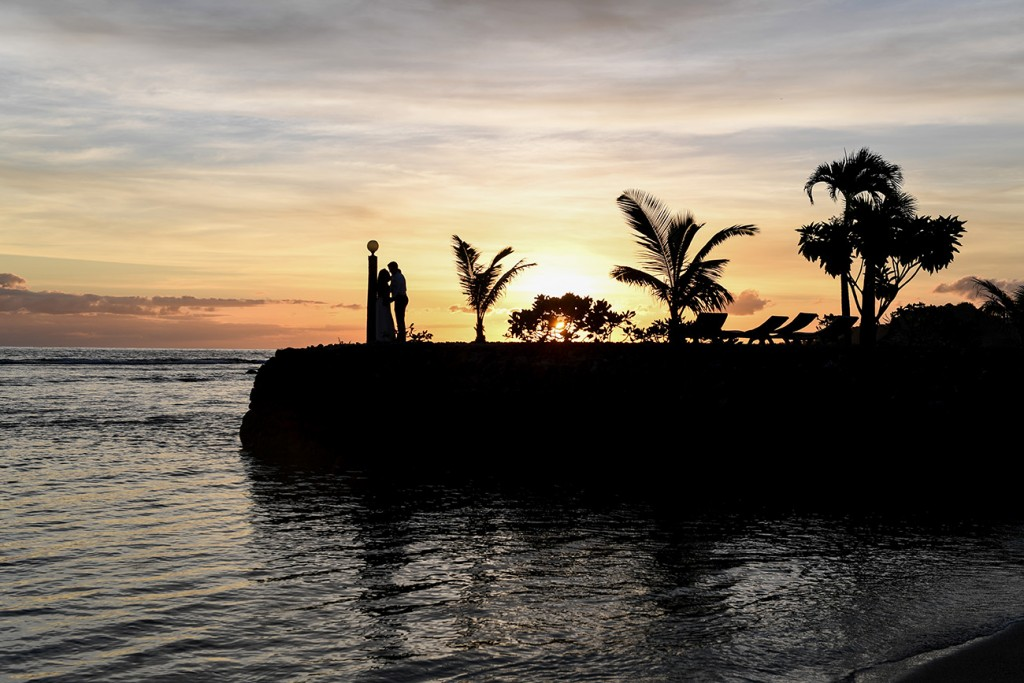 A silhouette of the palm trees, couple and the rocky dock against the fiery sunset
