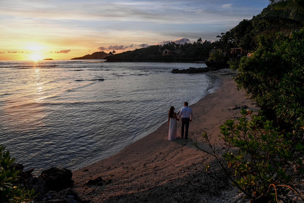 The newly weds stroll on the lonely Savasi beach at sunset