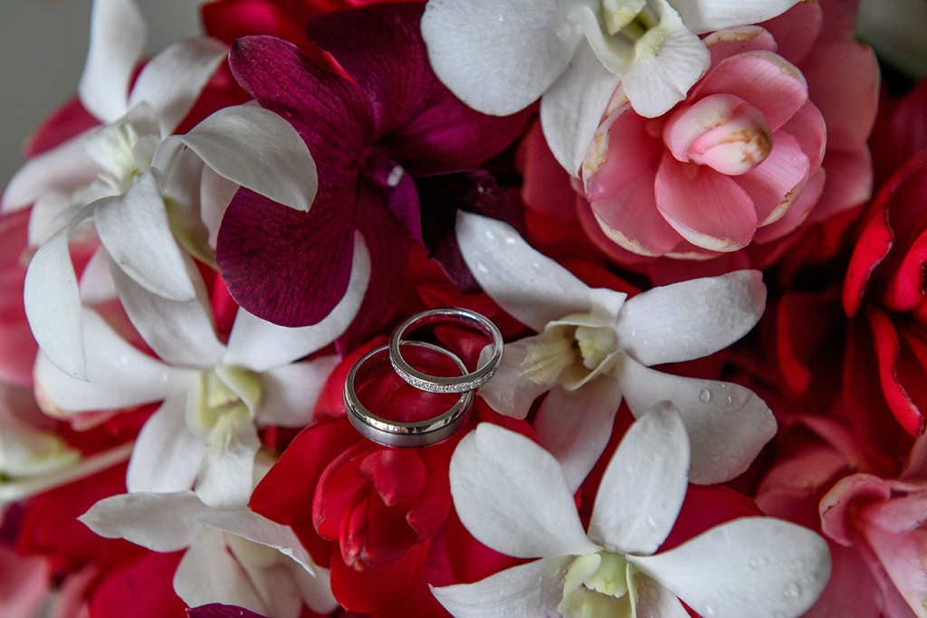 Silver and diamond rings nested on red and white frangipani flowers