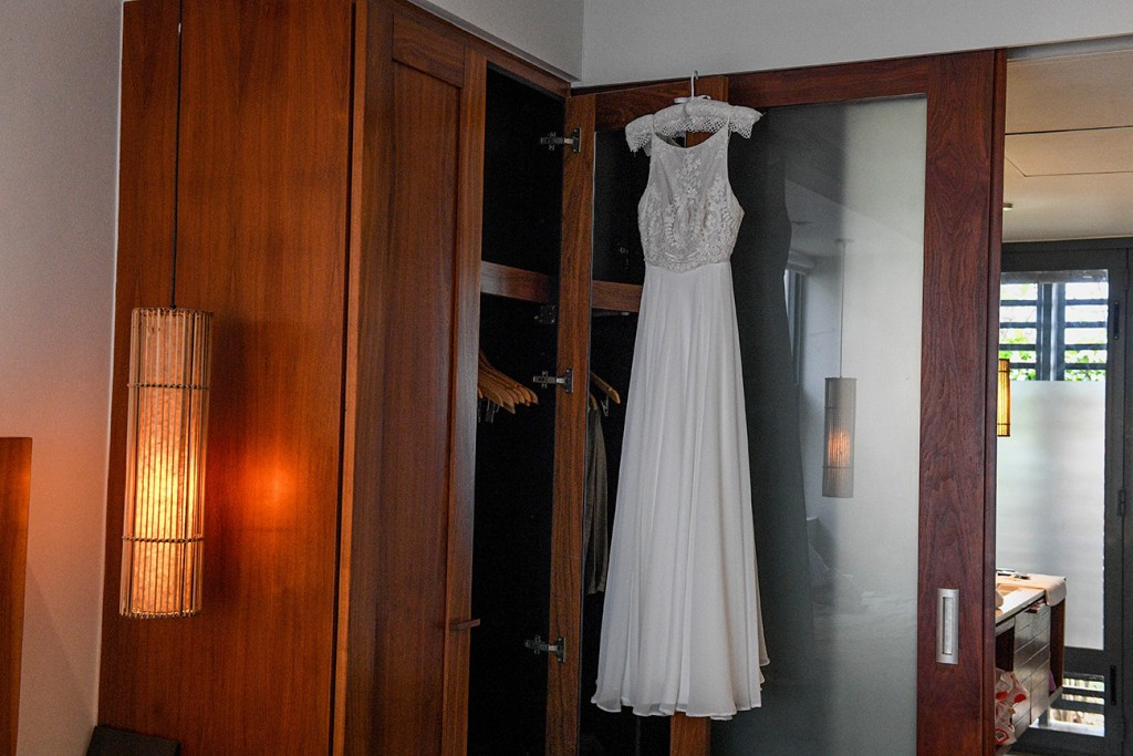 The stunning white lace sleeveless wedding gown hangs from the closet