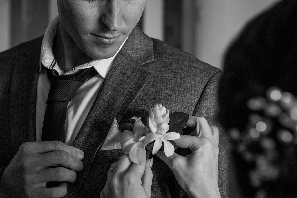 The bride adjusts the ginger flower boutonniere on her groom