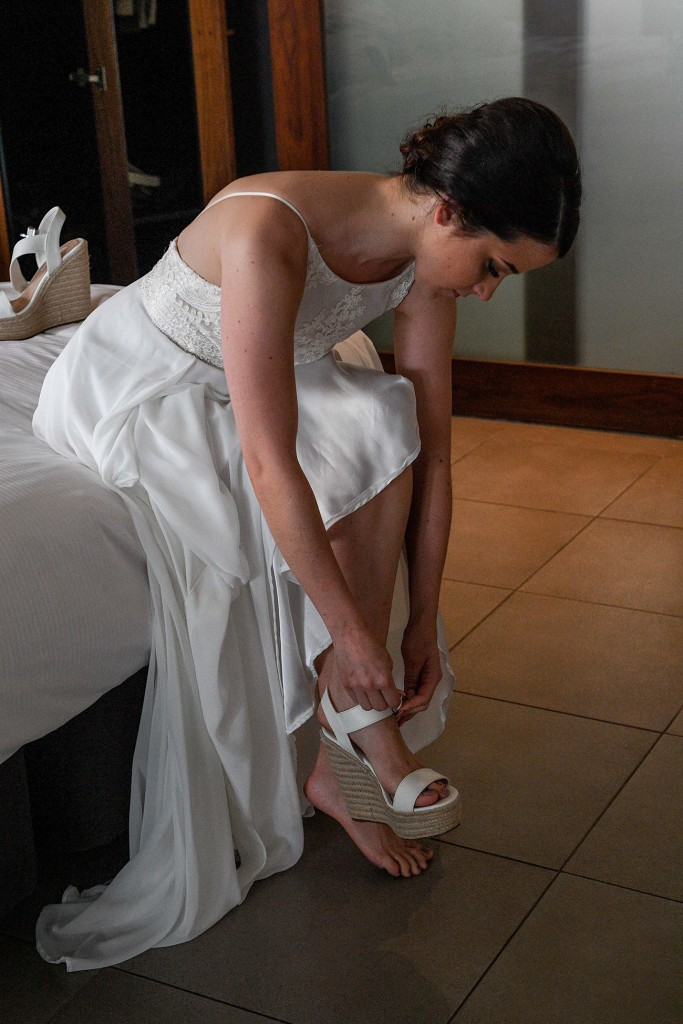 The bride straps on her wedges before the wedding