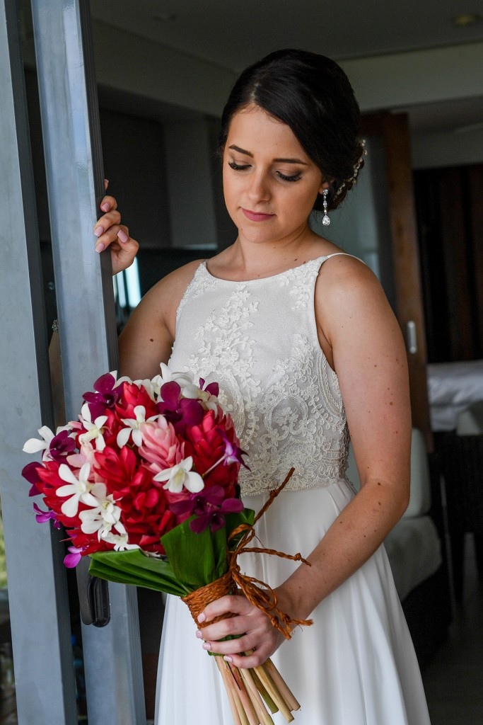 The bride stands in the doorway holding her stunning colourful island flower bouquet