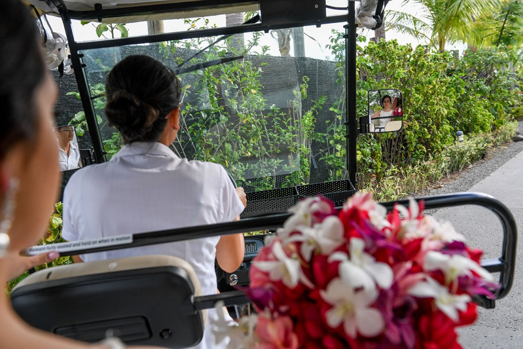 The bride is driven to the venue on a small golf cart