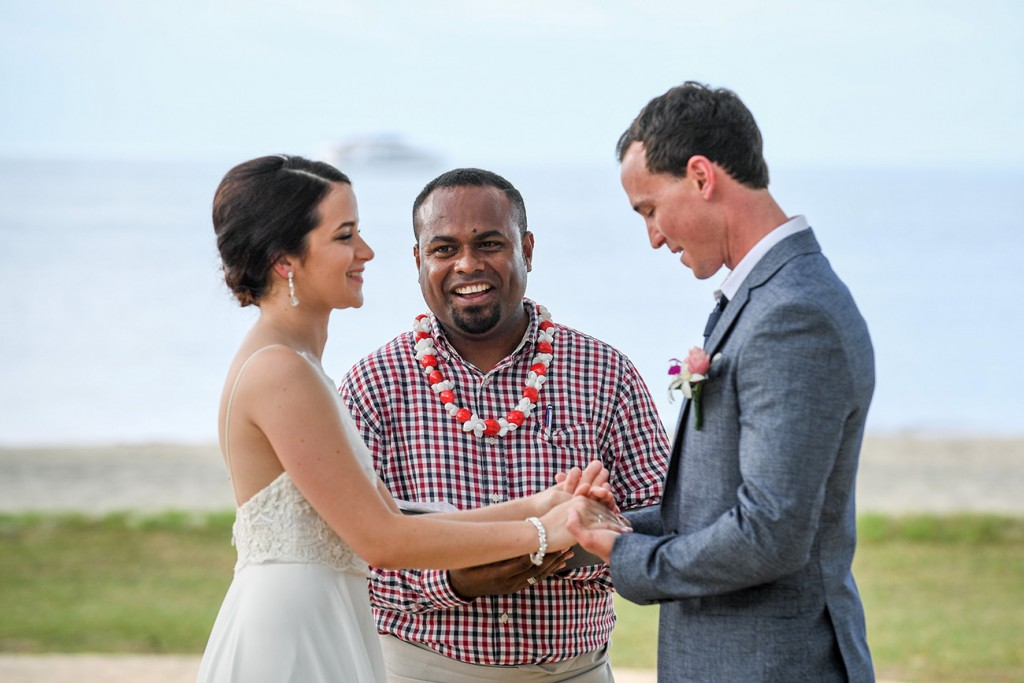 The emotional groom holds his bride's hands while saying his vows