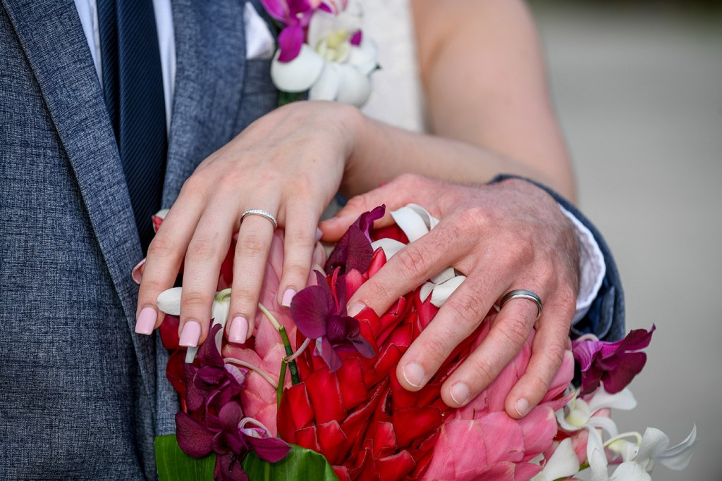 Newly married couple show off their rings on a bouquet of island flowers bouquet