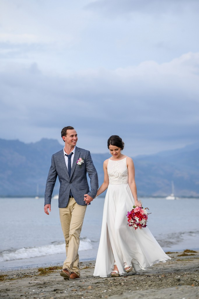 The newly married couple stroll on the beach against greying skies