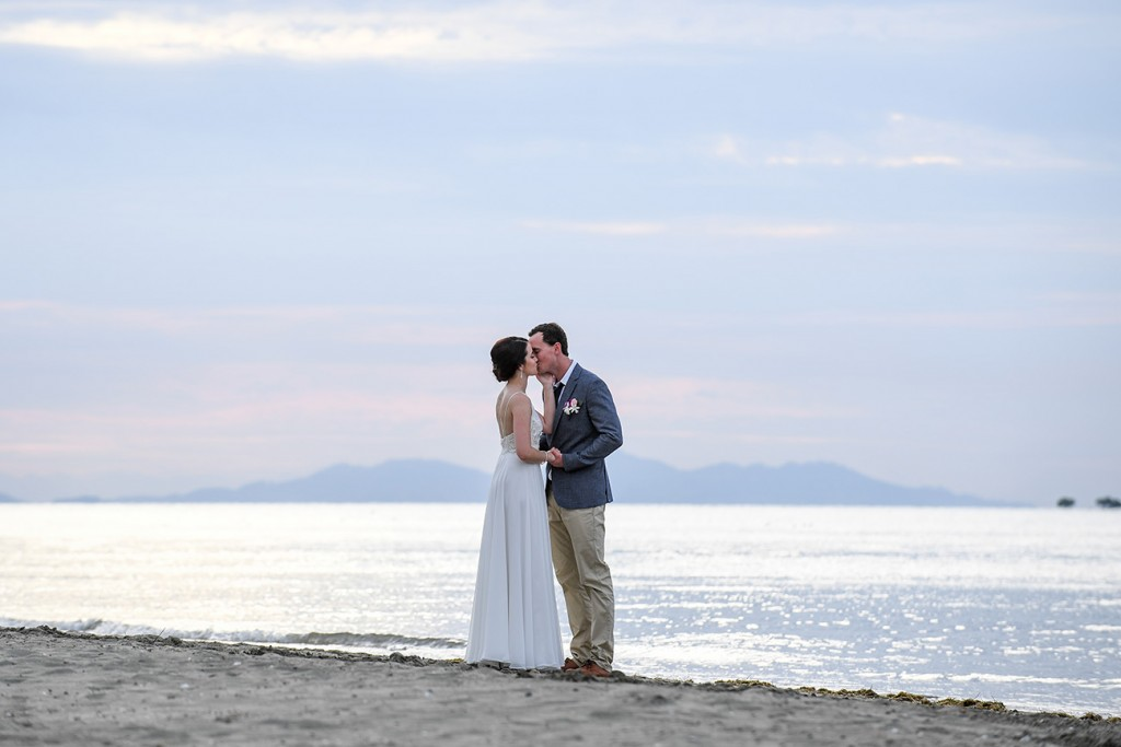 The newly-weds kiss on the shores of the Pacific Ocean at Denarau Fiji