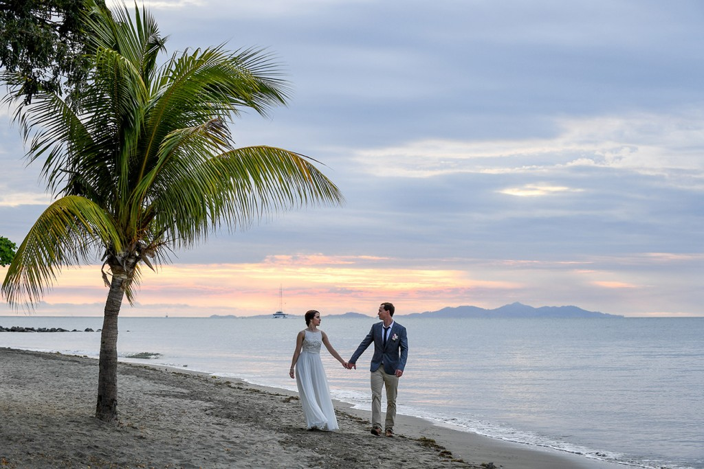 The newly-weds walk hand in hand on the shores of the Pacific Ocean