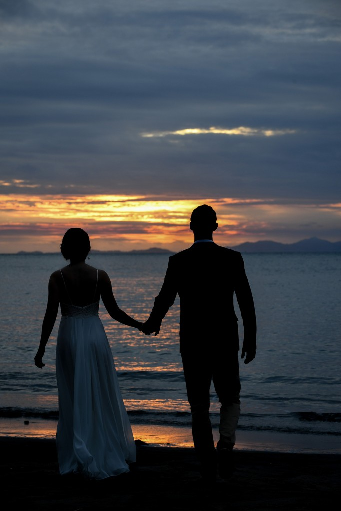 The bride and groom stroll towards the fiery sunset