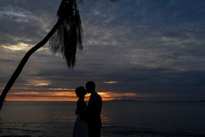 A silhouette of the couple kissing against the fiery sunset