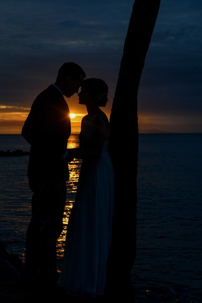 The couple is silhouetted by the fiery sun as they stand against a palm tree