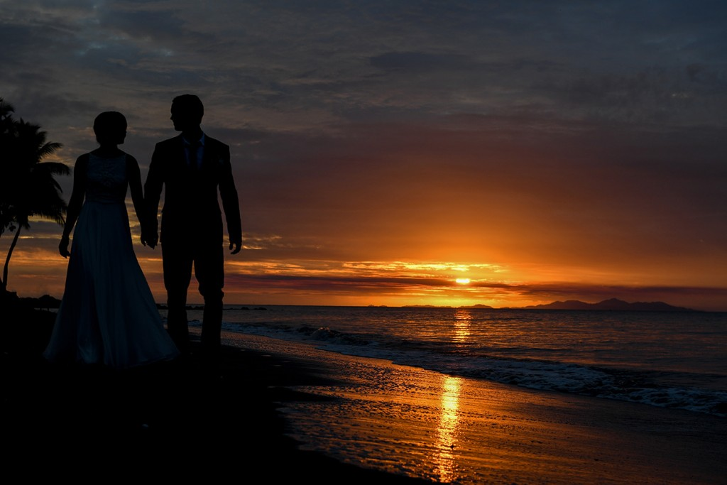 The couple is silhouetted as they stroll towards the fiery setting sun